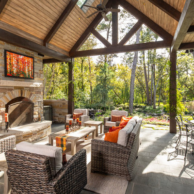 Example of a mountain style backyard patio design in Houston with a fireplace
