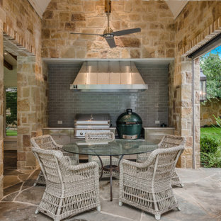 Example of a transitional stone patio design in Dallas with a roof extension