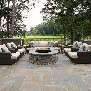 Esempio di un patio o portico minimal di medie dimensioni e dietro casa con un focolare, piastrelle e nessuna copertura