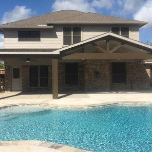 Aménagement d'une terrasse et balcon arrière craftsman de taille moyenne avec une dalle de béton et une extension de toiture.