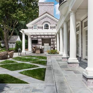 Foto di un ampio patio o portico classico dietro casa con piastrelle e una pergola