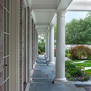 Ispirazione per un ampio patio o portico chic dietro casa con piastrelle e una pergola