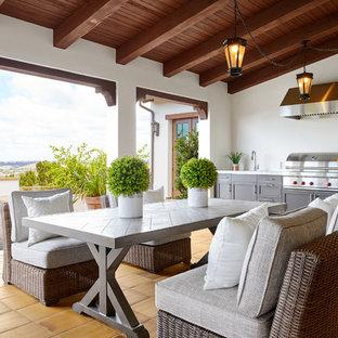 Ispirazione per un grande patio o portico mediterraneo dietro casa con pavimentazioni in cemento e un tetto a sbalzo
