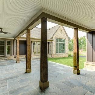 Esempio di un ampio patio o portico country con pavimentazioni in pietra naturale e un tetto a sbalzo