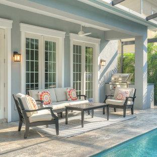 Idee per un patio o portico classico di medie dimensioni e dietro casa con piastrelle e un tetto a sbalzo