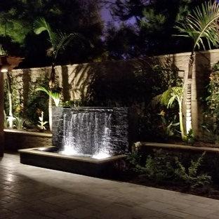 Immagine di un grande patio o portico tropicale dietro casa con pavimentazioni in cemento e una pergola
