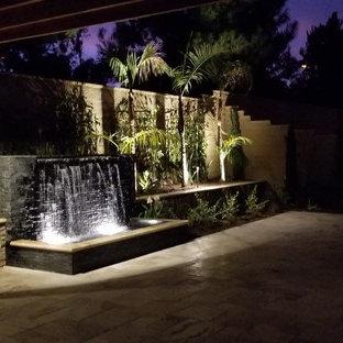 Aménagement d'une grande terrasse arrière exotique avec des pavés en béton et une pergola.