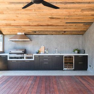 Idee per un patio o portico contemporaneo dietro casa con pedane e un tetto a sbalzo