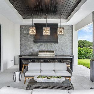 Esempio di un patio o portico stile marino dietro casa con pavimentazioni in cemento e un tetto a sbalzo