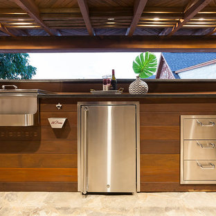 Example of a large trendy backyard stone patio kitchen design in Dallas with a pergola