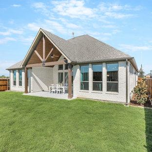Ispirazione per un patio o portico tradizionale di medie dimensioni e dietro casa con piastrelle e una pergola