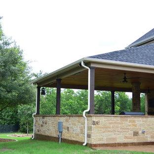 Foto di un ampio patio o portico bohémian dietro casa con un caminetto, cemento stampato e un tetto a sbalzo