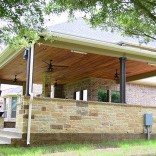 Esempio di un ampio patio o portico boho chic dietro casa con un caminetto, cemento stampato e un tetto a sbalzo