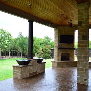 Ispirazione per un ampio patio o portico boho chic dietro casa con un caminetto, cemento stampato e un tetto a sbalzo