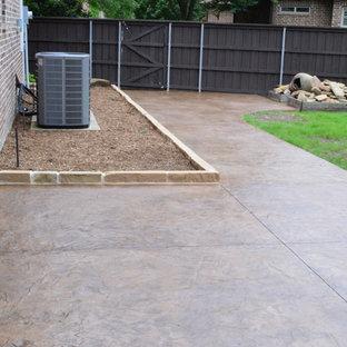 Esempio di un ampio patio o portico eclettico dietro casa con un caminetto, cemento stampato e un tetto a sbalzo