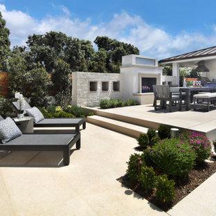 Esempio di un grande patio o portico minimal dietro casa con un caminetto e pavimentazioni in pietra naturale