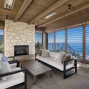 Immagine di un patio o portico costiero dietro casa con piastrelle, un tetto a sbalzo e un caminetto