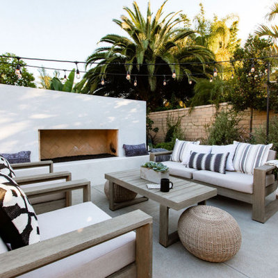 Patio - contemporary concrete patio idea in Orange County with a fireplace and no cover