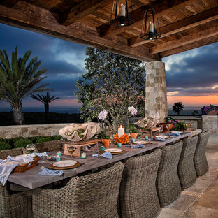 Example of a mid-sized tuscan backyard tile patio design in Orange County with a roof extension