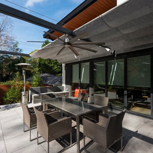 Design ideas for a modern back patio in Atlanta with an awning.