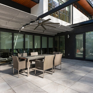 Example of a trendy backyard concrete paver patio design in Atlanta with an awning