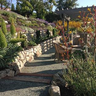 Immagine di un ampio patio o portico tradizionale dietro casa con un focolare, graniglia di granito e una pergola