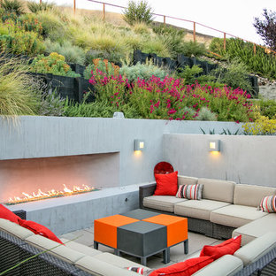 This is an example of a mid-sized contemporary backyard patio in San Francisco with a fire feature and concrete pavers.