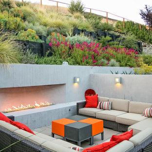 Foto di un patio o portico minimal di medie dimensioni e dietro casa con un focolare e pavimentazioni in cemento