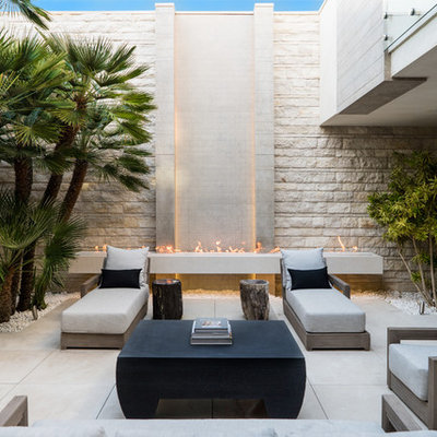 Example of a large trendy courtyard tile patio design in Phoenix with no cover and a fireplace