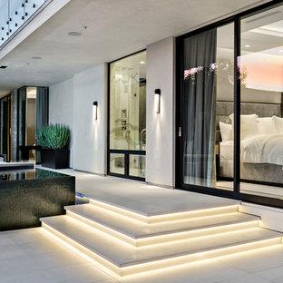 Idee per un patio o portico design di medie dimensioni e dietro casa con piastrelle e un tetto a sbalzo