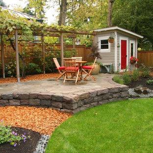 Ejemplo de patio tradicional, de tamaño medio, en patio trasero, con adoquines de piedra natural, fuente y cenador