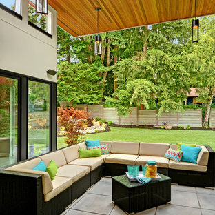 Example of a trendy concrete patio design in Seattle with a roof extension