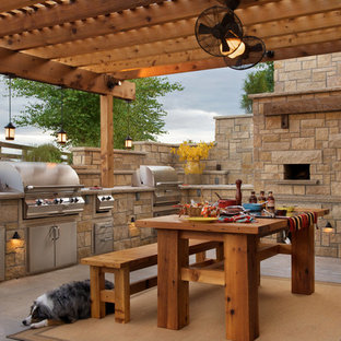 Mid-sized country backyard patio in Kansas City with an outdoor kitchen, concrete slab and a pergola.