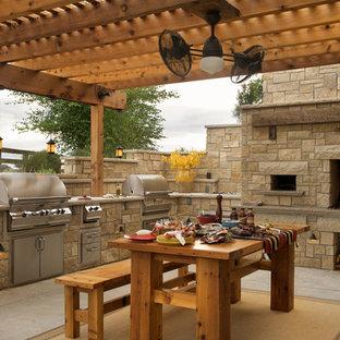 Idées déco pour une terrasse avec une cuisine extérieure arrière campagne de taille moyenne avec une dalle de béton et une pergola.