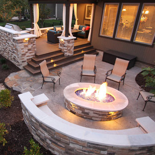 Example of a large trendy backyard stamped concrete patio design in Kansas City with a fire pit and a roof extension