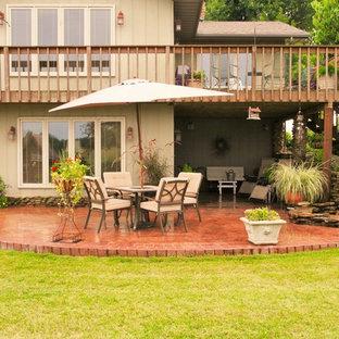 Idee per un grande patio o portico rustico dietro casa con fontane, un tetto a sbalzo e cemento stampato