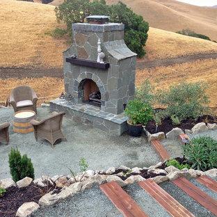 Immagine di un ampio patio o portico chic dietro casa con un focolare, graniglia di granito e una pergola