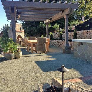 Foto di un ampio patio o portico chic dietro casa con un focolare, graniglia di granito e una pergola