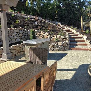 Foto di un ampio patio o portico chic dietro casa con graniglia di granito e una pergola