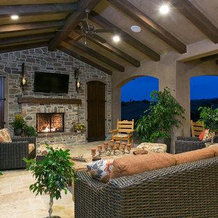 Exemple d'une terrasse chic avec un foyer extérieur et une extension de toiture.
