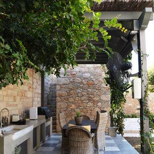 Kleine Mediterrane Pergola hinter dem Haus mit Outdoor-Küche in München