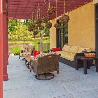 Ispirazione per un grande patio o portico tradizionale dietro casa con un focolare, cemento stampato e un tetto a sbalzo