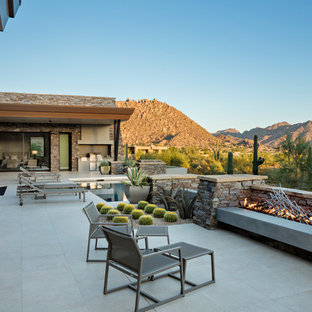 Southwest concrete paver patio photo in Phoenix with a fireplace and no cover