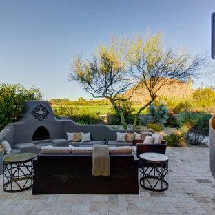 Foto di un ampio patio o portico american style dietro casa con pavimentazioni in pietra naturale, nessuna copertura e un caminetto