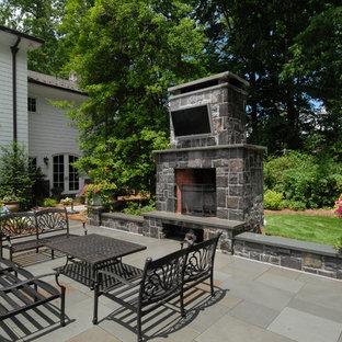 Idee per un ampio patio o portico vittoriano dietro casa con un focolare, pavimentazioni in pietra naturale e nessuna copertura