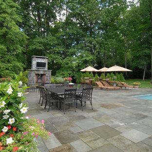 Ispirazione per un ampio patio o portico vittoriano dietro casa con un focolare, pavimentazioni in pietra naturale e nessuna copertura