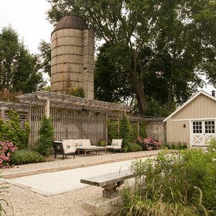 Immagine di un patio o portico country di medie dimensioni e nel cortile laterale con ghiaia e una pergola