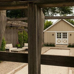 Esempio di un patio o portico country di medie dimensioni e nel cortile laterale con ghiaia e una pergola