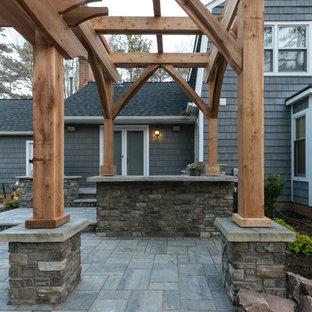 Idee per un patio o portico country di medie dimensioni e dietro casa con pavimentazioni in cemento e una pergola