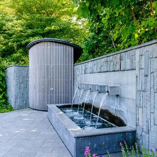 Esempio di un grande patio o portico industriale in cortile con fontane, nessuna copertura e pavimentazioni in cemento